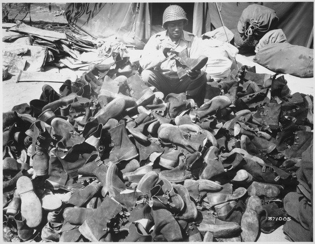 -Pfc._Robert_Askew...with_the_3278th_Quartermaster_Company,_examines_overshoes_which_have_been_turned_in._Overshoes_prov_-_NARA_-_531412.tif