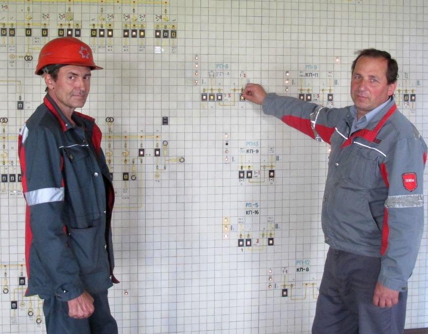 Виталий Чуйков, электромонтер по ремонту воздушных линий электропередач и Вадим Стопченко, старший мастер (сменный) возле энергосхемы завода.