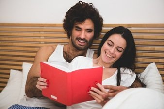 couple-smiling-while-reading-a-book-in-bed_23-2147595879
